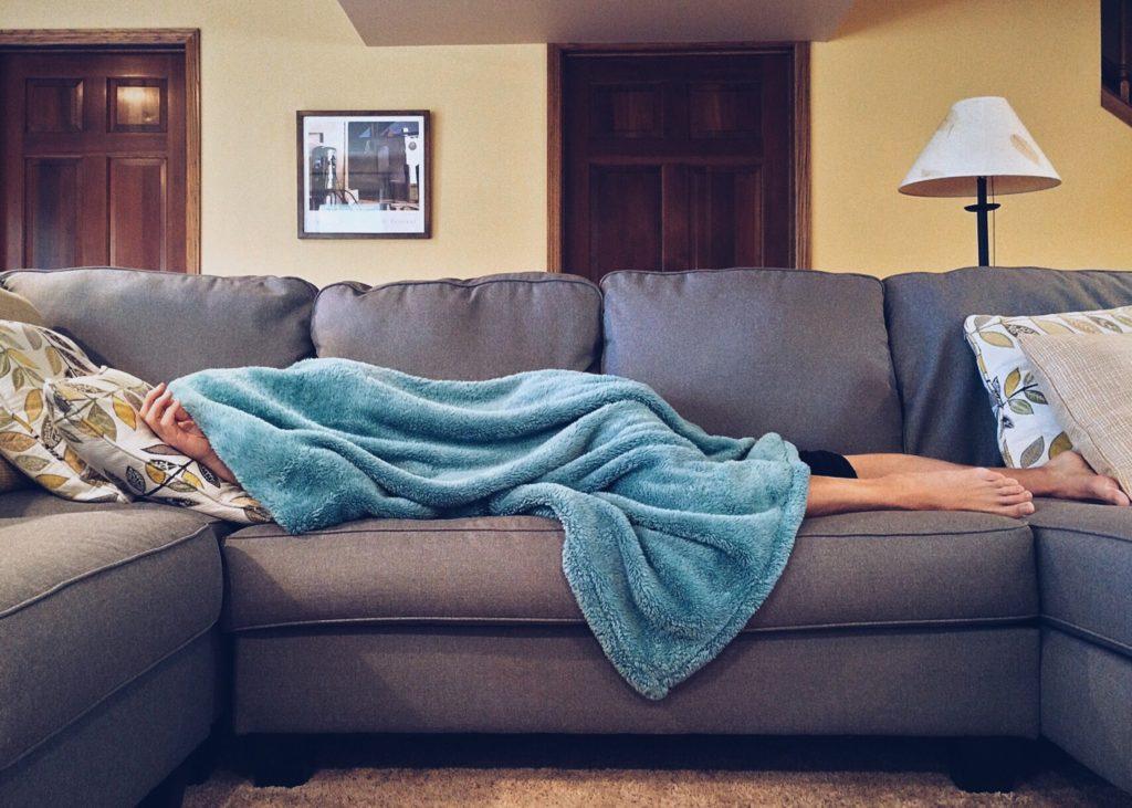 a kanapén a fejére húzott takaróval fekszik egy ember biztonságban, hogy ne hallja a szomszédok veszekedését.